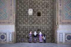 Kvinnor kikar in genom träporten i Uzbekistan